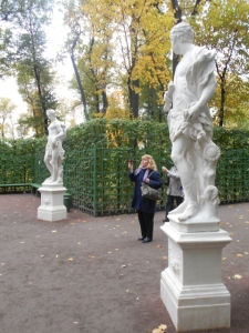 Surrounded by statues, Susan takes pictures. Note treillage fronting greenery